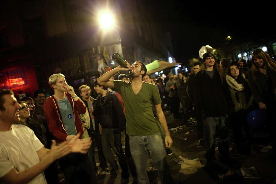 A man drinks champagne as a spontaneous party erupts in the intersection of East Pike Street and 10th Avenue after Barack Obama was announced as the winner, Referendum 74 appeared to be passing and a measure to legalize marijuana also seemed to be passing on Election Day, Tuesday, November 6, 2012. Photo: JOSHUA TRUJILLO / SEATTLEPI.COM