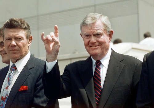 Former Texas coach Darrell Royal, right, holds up the 'hook'em horns' sign as he stands next to former Rice running back Dicky Maegle during a ceremony that named the two to the Cotton Bowl Hall of Fame, in Dallas, Thursday, May 28, 1998. Photo: ERIC GAY, AP / AP