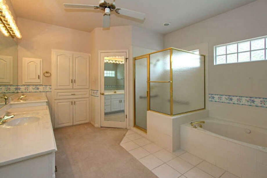A separate shower stall and bath and a row of incandescent lighting above the vanity are highlights of the master bathroom.