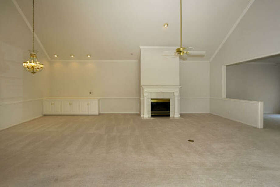 Additionally, the living room boasts a group of cabinets for storage, recessed lighting and two hanging fixtures.
