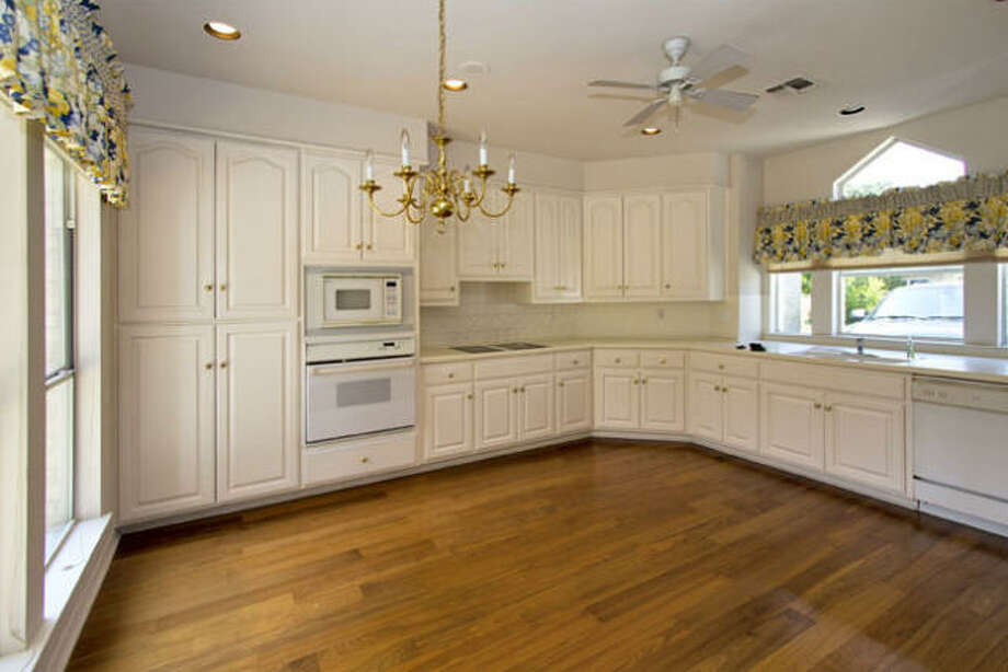 The kitchen has hardwood floors, a chandelier and large windows that let in a great deal of natural light.