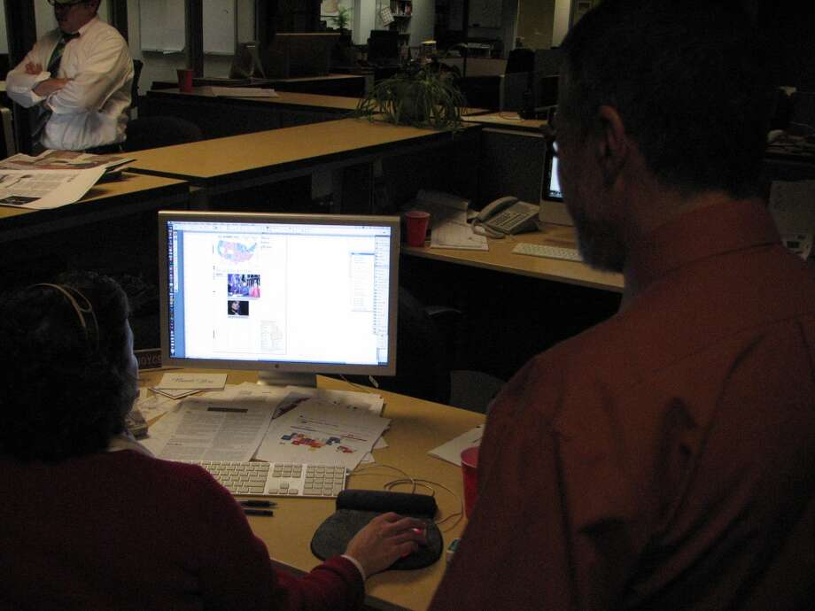 News editors Gary Hahn and Joyce Bassett look at an inside page.