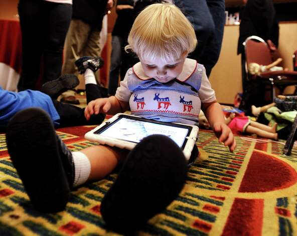 Democratic congressional candidate Nick Lampsons grandson Jack Shanning, 2, plays with his iPad while his family awaits results on the election for Congressional District 14 against  Randy Weber at the Holiday Inn on Walden Road in Beaumont on Tuesday, November 6,  2012. Photo taken: Randy Edwards/The Enterprise Photo: Randy Edwards