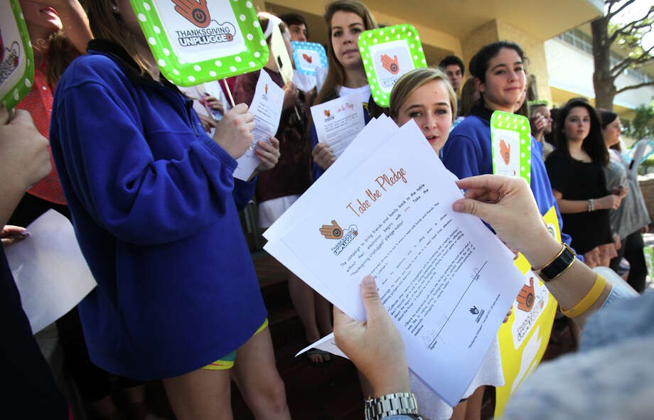 Hilary Shaw  hands out Thanksgiving Unplugged pledge forms to members of the Alamo Heights High School National Honor Society in front of the school. Photo: Bob Owen, San Antonio Express-News / © 2012 San Antonio Express-News