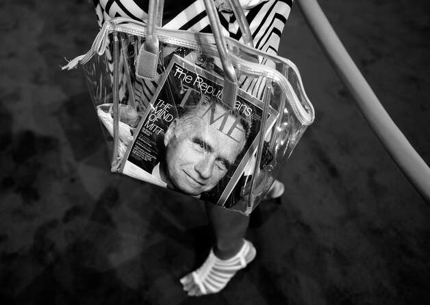 BLACK AND WHITE VERSION - A woman carries a purse with a Time Magazine featuring Republican presidential candidate Mitt Romney on the cover at the Tampa Bay Times Forum in Tampa, Florida, on August 28, 2012 ahead of the day's Republican National Convention events. The 2012 Republican National Convention is expected to host 2,286 delegates and 2,125 alternate delegates from all 50 states, the District of Columbia and five territories. AFP PHOTO Brendan SMIALOWSKI        (Photo credit should read BRENDAN SMIALOWSKI/AFP/GettyImages) Photo: BRENDAN SMIALOWSKI, AFP/Getty Images / 2012 AFP