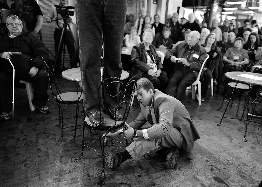 BLACK AND WHITE VERSION - A campaign staff holds on a chair that Republican presidential hopeful Mitt Romney stepped on to gain height to speak before a crowd at the Music Man Square in Mason City, Iowa on December 29, 2011. Mitt Romney has seized the lead in Iowa days before the unpredictable heartland state's caucus kicks off voting to decide the Republican presidential nominee, a new poll showed on December 28. Romney -- often described as the candidate to beat because of his campaign warchest and high-profile endorsements -- has struggled to boost his national support past roughly 25 percent of Republican voters. AFP Photo/Jewel Samad        (Photo credit should read JEWEL SAMAD/AFP/GettyImages) Photo: JEWEL SAMAD, AFP/Getty Images / 2012 AFP