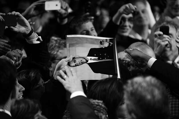 BLACK AND WHITE VERSION - A supporter holds a picture of US President Barack Obama during a campaign event at the University of Illinois at Chicago in Chicago, Illinois, on January 11, 2012. Obama sought to strike an implicit contrast with his most likely general election foe Mitt Romney, imploring big businesses to bring home US jobs outsourced overseas. White House officials insist that Obama has not yet started to focus on his bid for a second term in November, but is instead concentrating every day on his job, which he sees as reviving the economy and cutting unemployment. AFP Photo/Jewel Samad        (Photo credit should read JEWEL SAMAD/AFP/GettyImages) Photo: JEWEL SAMAD, AFP/Getty Images / 2012 AFP