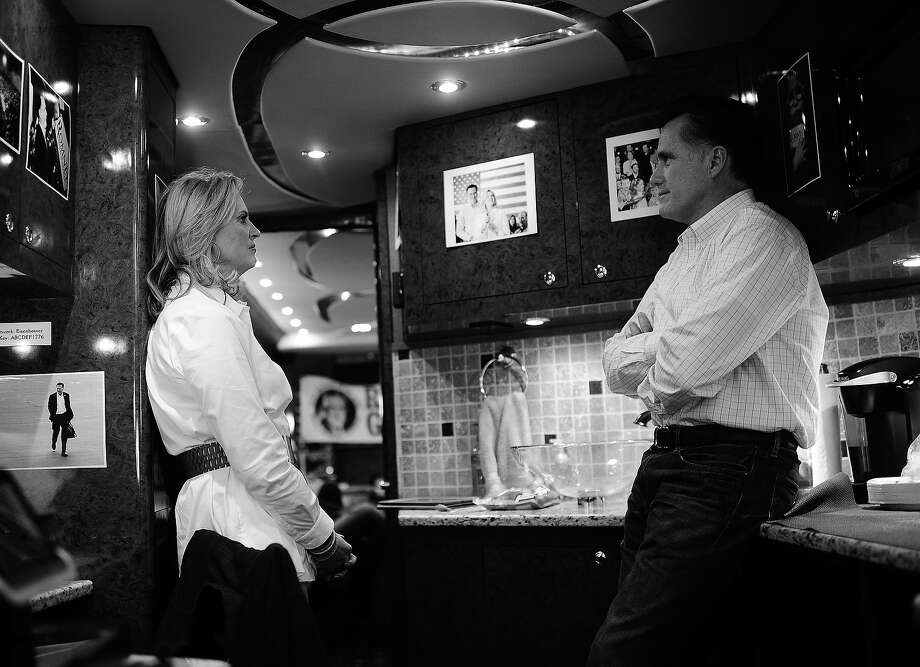 BLACK AND WHITE VERSION - Republican presidential hopeful Mitt Romney rides his campaign bus riding between Gilbert and Charleston, South Carolina, January 20, 2012. South Carolina will hold its Republican primary on January 21, 2012. At C, is Romney's son, Tagg and granddaughter Allie. AFP PHOTO/Emmanuel Dunand        (Photo credit should read EMMANUEL DUNAND/AFP/GettyImages) Photo: EMMANUEL DUNAND, AFP/Getty Images / 2012 AFP