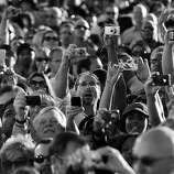 BLACK AND WHITE VERSION - A crowd of people photograph US President Barack Obama speaking at the Intel Ocotillo Campus in Chandler, Arizona, on January 25, 2012. Obama kicked off a three-day five-state tour, one day after his State of Union speech. Obama wants large tax hikes on millionaires to finance a fair economy for all, a populist vision aimed at convincing crisis-weary voters he merits a second White House term. In his annual State of the Union address -- which this year served as a grand kick-off of his 2012 reelection campaign, Obama played on rising anger over inequality in the wake of the 2008 economic collapse. AFP Photo/Jewel Samad        (Photo credit should read JEWEL SAMAD/AFP/GettyImages)