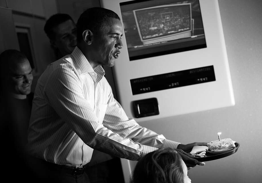 BLACK AND WHITE VERSION - US President Barack Obama offers a birthday cake to a reporter during the return flight from his announced trip to Afghanistan May 2, 2012.  Obama flew into Kabul in secret in the dead of night and signed the deal with President Hamid Karzai, cementing 10 years of US aid for Afghanistan after NATO combat troops leave in 2014. Most Afghans were asleep and he left after about six hours.  AFP PHOTO/Mandel NGAN        (Photo credit should read MANDEL NGAN/AFP/GettyImages) Photo: MANDEL NGAN, AFP/Getty Images / 2012 AFP