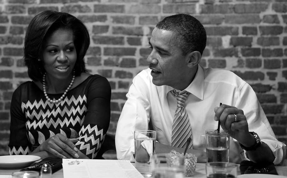 "BLACK AND WHITE VERSION - US President Barack Obama and First Lady Michelle Obama have dinner with winners of a Democratic campaign contest at the Boundary Road restaurant in Washington, DC, March 8, 2012. Three winners and their guests each won the ""Dinner with Barack and Michelle"" contest, as part of a campaign fundraiser among grassroots supporters from around the country. AFP PHOTO / Saul LOEB        (Photo credit should read SAUL LOEB/AFP/GettyImages) Photo: SAUL LOEB, AFP/Getty Images / 2012 AFP"