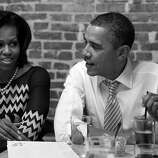 "BLACK AND WHITE VERSION - US President Barack Obama and First Lady Michelle Obama have dinner with winners of a Democratic campaign contest at the Boundary Road restaurant in Washington, DC, March 8, 2012. Three winners and their guests each won the ""Dinner with Barack and Michelle"" contest, as part of a campaign fundraiser among grassroots supporters from around the country. AFP PHOTO / Saul LOEB        (Photo credit should read SAUL LOEB/AFP/GettyImages)"