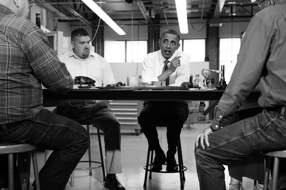 BLACK AND WHITE VERSION - US President Barack Obama smiles while speaking with Bronson Harwood (L) and David Palmer (C) during a round table at Lorain County Community College April, 18, 2012 in Elyria, Ohio.  President Obama traveled to the college to attend a round table discussion and deliver a speech about the economy.        (Photo credit should read BRENDAN SMIALOWSKI/AFP/GettyImages) Photo: BRENDAN SMIALOWSKI, AFP/Getty Images / 2012 AFP
