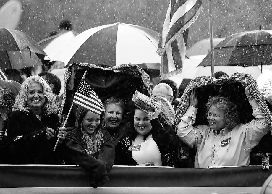 BLACK AND WHITE VERSION - Republican presidential hopeful Mitt Romney supporters await his arrival under rain at a campaign rally in Gilbert, South Carolina, January 20, 2012. South Carolina will hold its Republican primary on January 21, 2012.  AFP PHOTO/Emmanuel Dunand        (Photo credit should read EMMANUEL DUNAND/AFP/GettyImages) Photo: EMMANUEL DUNAND, AFP/Getty Images / 2012 AFP