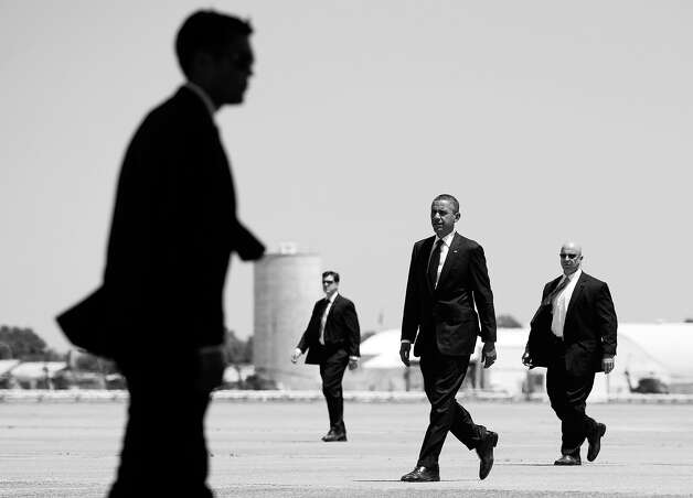 BLACK AND WHITE VERSION - US President Barack Obama, surrounded by the US Secret Service, walks to Air Force One after escorting First Lady Michelle Obama to her airplane at Hunter Army Airfield in Hinesville, Georgia, April 27, 2012, after visiting with US troops at Fort Stewart in Georgia. Michelle Obama is traveling to a fundraiser as President Obama returns to Washington.     AFP PHOTO/Saul LOEB        (Photo credit should read SAUL LOEB/AFP/GettyImages) Photo: SAUL LOEB, AFP/Getty Images / 2012 AFP