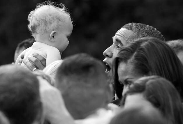BLACK AND WHITE VERSION - US President Barack Obama holds a baby during an Independence Day celebration for military members and their families and members of the administration the South Lawn of the White House in Washington, DC, July 4, 2012. AFP PHOTO / Saul LOEB        (Photo credit should read SAUL LOEB/AFP/GettyImages) Photo: SAUL LOEB, AFP/Getty Images / 2012 AFP
