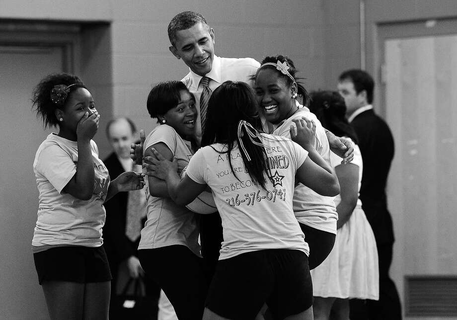 """BLACK AND WHITE VERSION - US President Barack Obama greets girls playing at the Boys and Girls Club of Cleveland in Cleveland, Ohio, on June 14, 2012. Obama's campaign savagely mocked Mitt Romney as """"out of touch"""" with ordinary Americans Wednesday with a web video featuring a highlight reel of the Republican's gaffes. The move came as Romney, a multi-millionaire former venture capitalist, argues that it is Obama that has lost touch with the economic pain stalking the US heartland, and as each candidate tries to outdo the other in professing deep empathy with the middle-class. AFP PHOTO/Jewel Samad        (Photo credit should read JEWEL SAMAD/AFP/GettyImages) Photo: JEWEL SAMAD, AFP/Getty Images / 2012 AFP"""