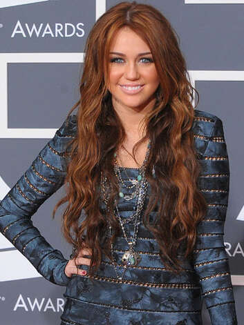 Miley Cyrus From her fake and baked skin to her over-done red extensions, Miley looked anything but au naturel at the 2010 Grammy Awards.    Reprinted with Permission of Hearst Communications, Inc. Originally Published: 60 Best Celebrity Makeovers of All Time Photo: Getty Images / 2010 Getty Images