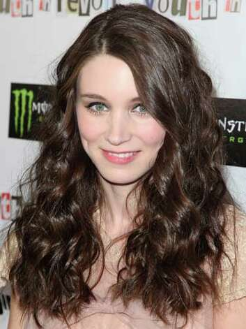 Rooney Mara Rooney's cascading brunette curls and sheer top adorned with an oversized bow and lace relay her feminine fashion sense at the 2010 Youth in Revolt premiere.  Reprinted with Permission of Hearst Communications, Inc. Originally Published: 60 Best Celebrity Makeovers of All Time Photo: Getty Images / 2010 Getty Images