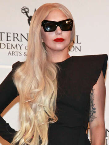 Lady Gaga Mother Monster has toned down her flamboyant style for more classic glamour wearing red lipstick, flowing blonde curls, and a lengthy black dress with over-the-top shoulder pads at the 2011 International Emmy Awards.  Reprinted with Permission of Hearst Communications, Inc. Originally Published: 60 Best Celebrity Makeovers of All Time Photo: Getty Images