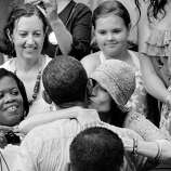 BLACK AND WHITE VERSION - A supporter kisses US President Barack Obama after he spoke at a rain-soaked campaign event on July 14, 2012 at Walkerton Tavern & Gardens in Glen Allen, Virginia. Obama is campaigning in Virginia for the second straight day ahead of the November presidential election.    AFP PHOTO/Mandel NGAN        (Photo credit should read MANDEL NGAN/AFP/GettyImages)