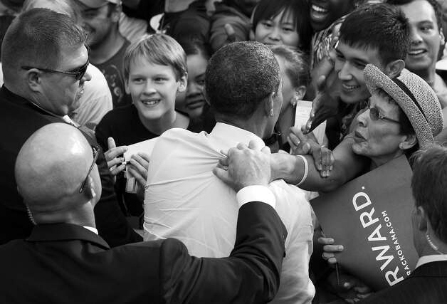 BLACK AND WHITE VERSION - Members of the US Secret Service remove a supporter's hand from the back of US President Barack Obama as he greets supporters during a campaign event at Colorado State University in Fort Collins, Colorado, August 28, 2012. AFP PHOTO / Saul LOEB        (Photo credit should read SAUL LOEB/AFP/GettyImages) Photo: SAUL LOEB, AFP/Getty Images / 2012 AFP