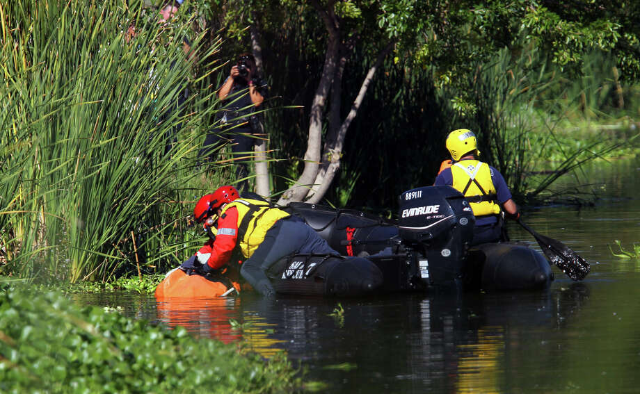 San Antonio firefighters remove a body that was found in Woodlawn Lake Wednesday morning about 9:30 a.m. . Trinidad Escamilla,62, said he was at the park at Woodlawn Lake and saw the body floating near the shore and notified authorities. The scene is currently being investigated by San Antonio police. Photo: John Davenport/Express-News