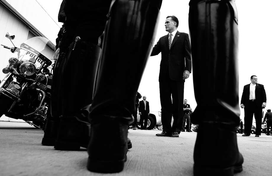 BLACK AND WHITE VERSION - US Republican presidential candidate Mitt Romney greets policemen before boarding his campaign plane on October 4, 2012 in Denver, Colorado. AFP PHOTO/Jewel Samad        (Photo credit should read JEWEL SAMAD/AFP/GettyImages) Photo: JEWEL SAMAD, AFP/Getty Images / 2012 AFP