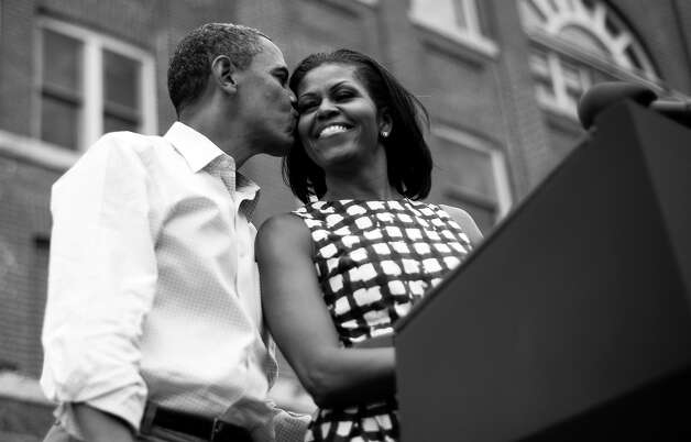 BLACK AND WHITE VERSION - US President Barack Obama (L) kisses First Lady Michelle Obama (R) as they arrive to deliver remarks during a campaign event at the Alliant Energy Amphitheater in Dubuque, Iowa, August 15, 2012, during his three-day campaign bus tour across the state.      AFP PHOTO/Jim WATSON        (Photo credit should read JIM WATSON/AFP/GettyImages) Photo: JIM WATSON, AFP/Getty Images / 2012 AFP
