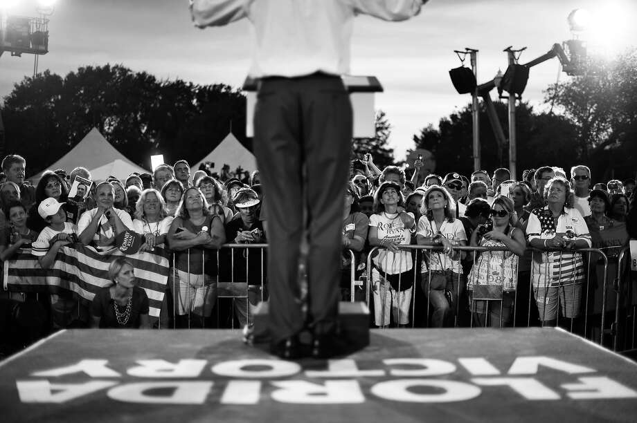 """BLACK AND WHITE VERSION - US Republican presidential candidate Mitt Romney speaks during a campaign event on October 5, 2012 in St. Petersburg, Florida. Fresh from a much-needed debate victory, Republican challenger Mitt Romney said his earlier remarks dismissing 47 percent of Americans as government dependents were """"completely wrong."""" The admission came amid a campaign reset that shocked Democrat Barack Obama at Wednesday's debate, in which his invigorated rival for the White House vowed to fight for middle class families that Romney said were being """"crushed"""" by the president's policies. AFP PHOTO/Jewel Samad        (Photo credit should read JEWEL SAMAD/AFP/GettyImages) Photo: JEWEL SAMAD, AFP/Getty Images / 2012 AFP"""