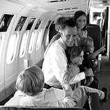BLACK AND WHITE VERSION - US Republican presidential candidate Mitt Romney plays with the five children of his son Josh aboard his plane on September 18, 2012 in Salt Lake City.     AFP PHOTO/Nicholas KAMM        (Photo credit should read NICHOLAS KAMM/AFP/GettyImages)