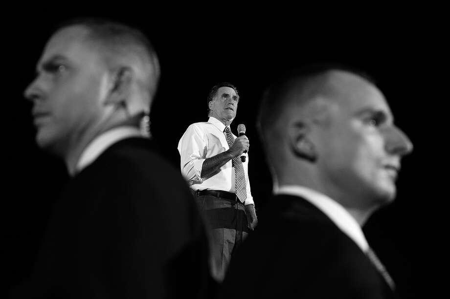 BLACK AND WHITE VERSION - US Republican presidential candidate Mitt Romney speaks as secret service members keep guard during campaign rally on October 4, 2012 in Fishersville, Virginia. AFP PHOTO/Jewel Samad        (Photo credit should read JEWEL SAMAD/AFP/GettyImages) Photo: JEWEL SAMAD, AFP/Getty Images / 2012 AFP
