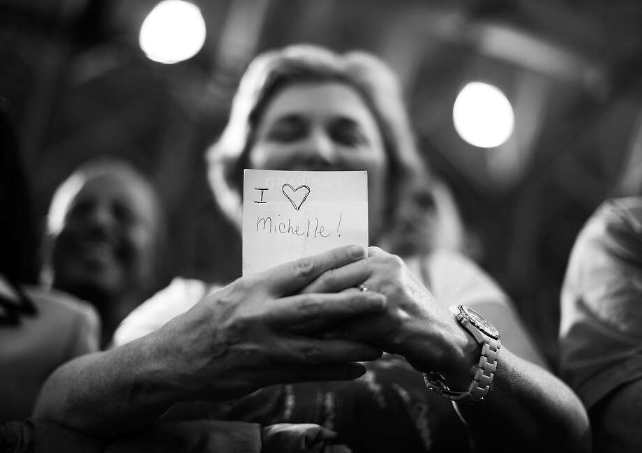 """BLACK AND WHITE VERSION - A supporter holds a note reads """"I love Michelle"""" as US President Barack Obama speaks at a campaign rally at the Bowling Green State University on September 26, 2012 in Bowling Green, Ohio. Obama has widened his lead in the two main battleground states in the 2012 White House race as well as in Pennsylvania, according to a new opinion poll released Wednesday. AFP PHOTO/Jewel Samad        (Photo credit should read JEWEL SAMAD/AFP/GettyImages) Photo: JEWEL SAMAD, AFP/Getty Images / 2012 AFP"""