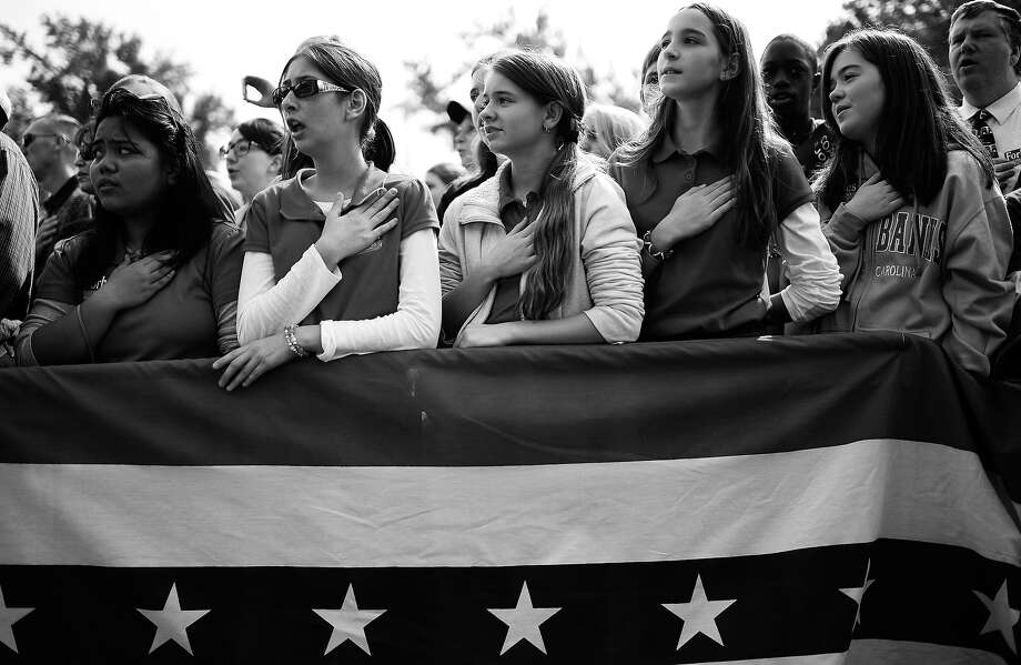 BLACK AND WHITE VERSION  US Republican presidential candidate Mitt Romney supporters sing the US National Anthem as he holds a campaign rally at The Grove, in Chesapeake, Virginia, October 17, 2012. AFP PHOTO/Emmanuel DUNAND Photo: EMMANUEL DUNAND, AFP/Getty Images / 2012 AFP