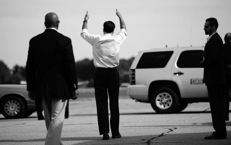 BLACK AND WHITE VERSION  US Republican presidential candidate Mitt Romney gives the thumb up to pilots greeting him prior to board his campaign plane at Norfolk International Airport in Norfolk, Virginia, October 17, 2012. AFP PHOTO/Emmanuel DUNAND Photo: EMMANUEL DUNAND, AFP/Getty Images / 2012 AFP