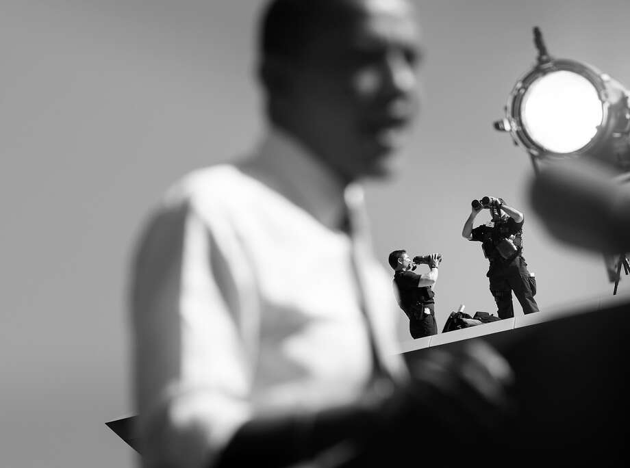 """BLACK AND WHITE VERSION  Members of the Secret Service watch as US President Barack Obama speaks during a rally at Veterans Memorial Park October 18, 2012 in Manchester, New Hampshire. Obama is traveling to New Hampshire and New York to attend campaign events before appearing on the """"Daily Show"""" and attending the 67th Annual Alfred E. Smith Memorial Foundation dinner in New York City.  AFP PHOTO/Brendan SMIALOWSKI Photo: BRENDAN SMIALOWSKI, AFP/Getty Images / 2012 AFP"""