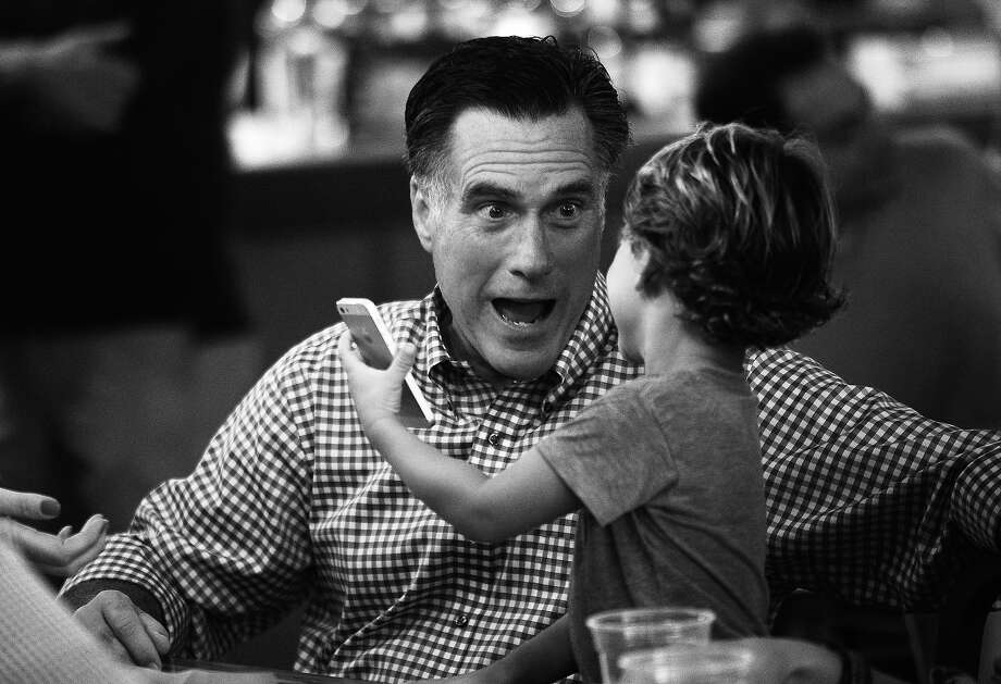 BLACK AND WHITE VERSION  US Republican presidential candidate Mitt Romney talks with grandson Miles while having dinner with members of his family at BurgerFi restaurant in Delray Beach, Florida, on October 21, 2012.     AFP PHOTO/Emmanuel DUNAND Photo: EMMANUEL DUNAND, AFP/Getty Images / 2012 AFP