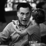 BLACK AND WHITE VERSION  US Republican presidential candidate Mitt Romney talks with grandson Miles while having dinner with members of his family at BurgerFi restaurant in Delray Beach, Florida, on October 21, 2012.     AFP PHOTO/Emmanuel DUNAND
