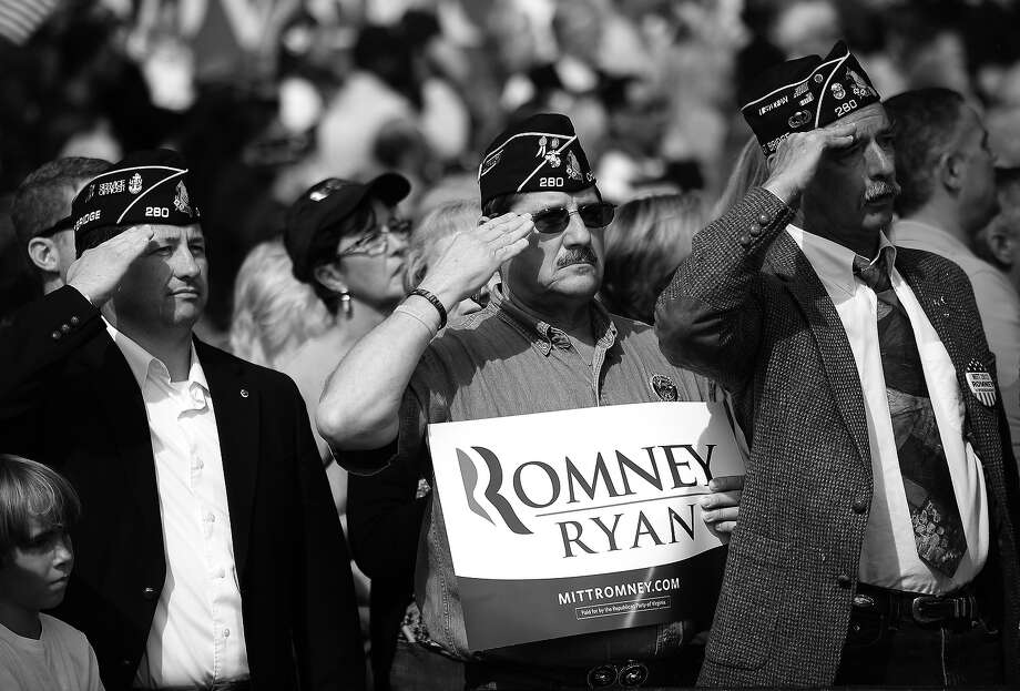 BLACK AND WHITE VERSION US military veterans salute while attending a Republican presidential candidate Mitt Romney rally at The Grove, in Chesapeake, Virginia, October 17, 2012. AFP PHOTO/Emmanuel DUNAND Photo: EMMANUEL DUNAND, AFP/Getty Images / 2012 AFP