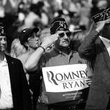 BLACK AND WHITE VERSION US military veterans salute while attending a Republican presidential candidate Mitt Romney rally at The Grove, in Chesapeake, Virginia, October 17, 2012. AFP PHOTO/Emmanuel DUNAND