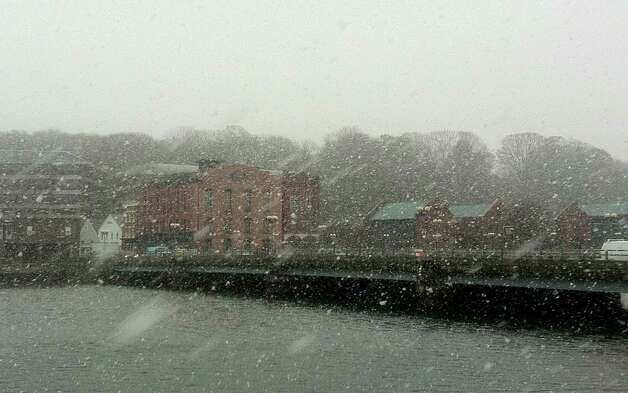 Snow falls steadily at midday Wednesday over the Saugatuck River, with National Hall in the distance, as a nor'easter moved into the region. Westport CT 11/7/12 Photo: Paul Schott / Westport News