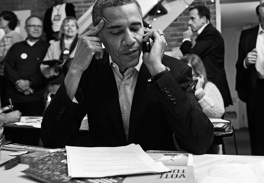 BLACK AND WHITE VERSION US President Barack Obama calls volunteers as he visits a campaign office in
