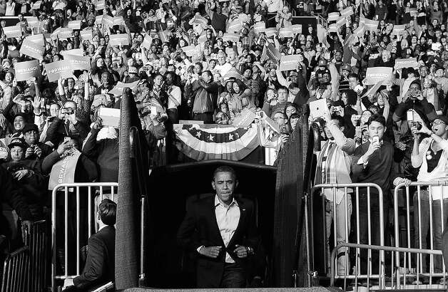 BLACK AND WHITE VERSION US President Barack Obama takes the stage during a campaign rally in Columbus, Ohio, on November 5, 2012. After a grueling 18-month battle, the final US campaign day arrived Monday for Obama and Republican rival Mitt Romney, two men on a collision course for the world's top job. The candidates have attended hundreds of rallies, fundraisers and town halls, spent literally billions on attack ads, ground games, and get out the vote efforts, and squared off in three intense debates. AFP PHOTO/Jewel Samad Photo: JEWEL SAMAD, AFP/Getty Images / 2012 AFP