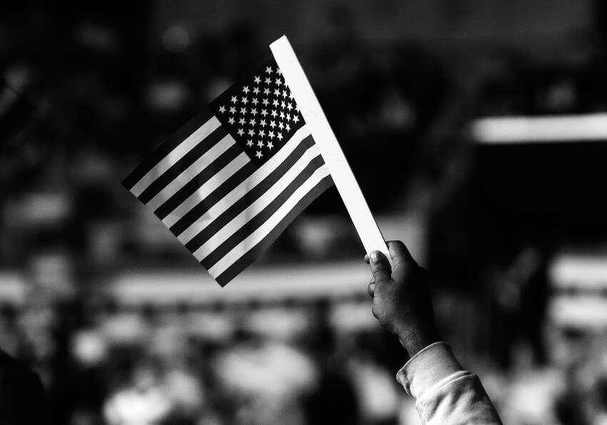 BLACK AND WHITE VERSION A supporter waves a US flag as President Barack Obama speaks at a campaign r
