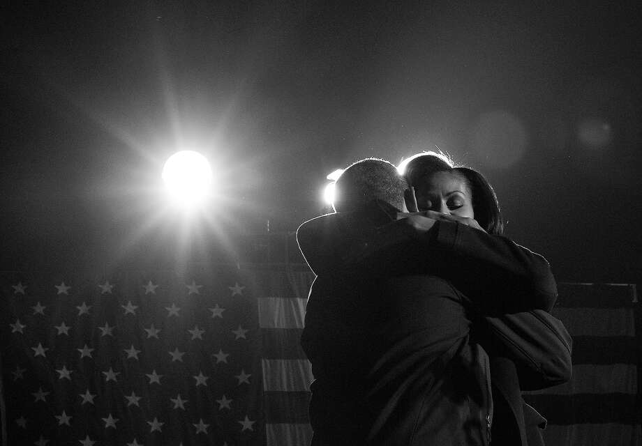 BLACK AND WHITE VERSION US President Barack Obama embraces First Lady Michelle Obama after speaking at his last campaign rally in Des Moines, Iowa, on November 5, 2012. After a grueling 18-month battle, the final US campaign day arrived Monday for Obama and Republican rival Mitt Romney, two men on a collision course for the world's top job. The candidates have attended hundreds of rallies, fundraisers and town halls, spent literally billions on attack ads, ground games, and get out the vote efforts, and squared off in three intense debates. AFP PHOTO/Jewel Samad Photo: JEWEL SAMAD, AFP/Getty Images / 2012 AFP
