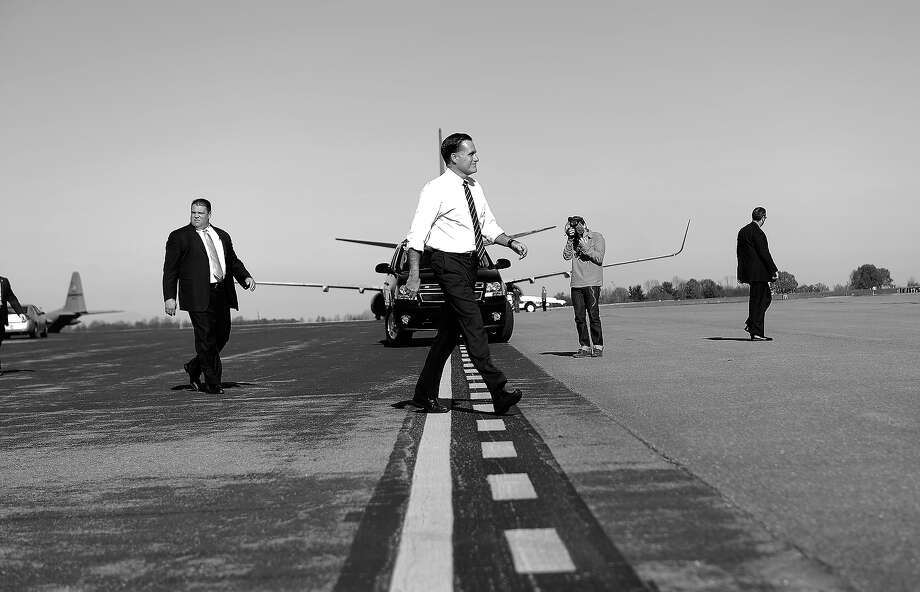 BLACK AND WHITE VERSION US Republican Presidential candidate Mitt Romney walks towards his campaign plane after a rally at Lynchburg regional airport in Lynchburg, Virginia, on November 5, 2012. After a grueling 18-month battle, the final US campaign day arrived for President Barack Obama and Republican rival Mitt Romney, two men on a collision course for the world's top job. The candidates have attended hundreds of rallies, fundraisers and town halls, spent literally billions on attack ads, ground games, and get out the vote efforts, and squared off in three intense debates.   AFP PHOTO/Emmanuel DUNAND Photo: EMMANUEL DUNAND, AFP/Getty Images / 2012 AFP