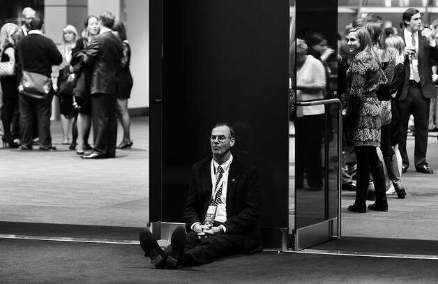 BLACK AND WHITE VERSION A supporter of US Presidential candidate Mitt Romney sits on the floor on election night November 6, 2012 in Boston Massachusetts. AFP PHOTO/ TIMOTHY A. CLARY Photo: TIMOTHY A. CLARY, AFP/Getty Images / 2012 AFP