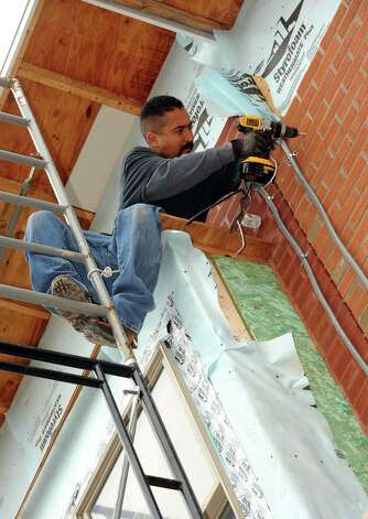 Volunteer electrician Gabriel Machine works on the wiring of a Habitat for Humanity home under construction on  Alexander Street in Albany, NY Wednesday Oct. 24, 2012. (Michael P. Farrell/Times Union) Photo: Michael P. Farrell