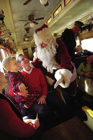 Santa welcomes little ones to a ride on the vintage train dubbed the North Pole Express in Grapevine. Photo: Courtesy Grapevine CVB