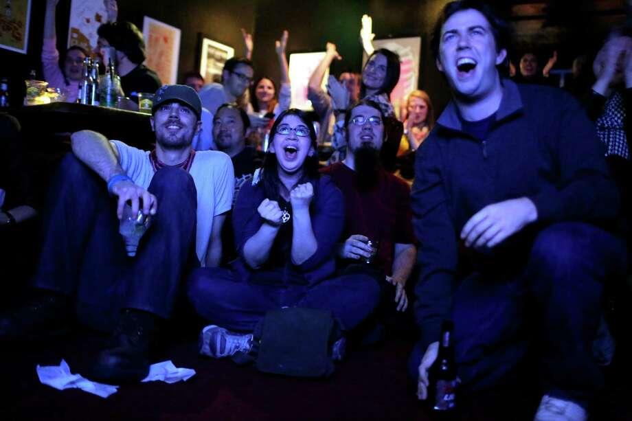 From right to left, Matt Farler, Andrew Hopkins, Allison Miller and Austin Derck all scream in unison as President Barack Obama's projected win flashes across a TV tuned to CCN on election night Tuesday, November 6, 2012, at Neumos on Capitol Hill in Seattle, Wash. Crowds flocked to return parties hosted by a number of bars in the area to wait out final ballot results. In addition to President Barack Obama's reelection, Referendum 74 and I-502 were both passed in Washington state. Photo: JORDAN STEAD / THE EMERALD COLLECTIVE / FOR SEATTLEPI.COM